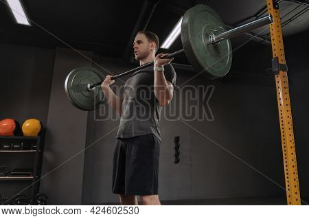 Male Bodybuilder Doing Military Press At Dark Gym. Weightlifter Holding Barbell On Chest, Preparing