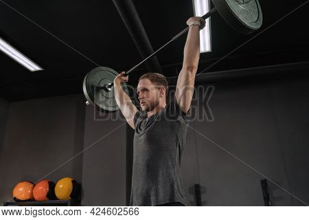Portrait Of Muscular Weightlifter Doing An Exercise With A Barbell. Barbell Above The Head. Strong A
