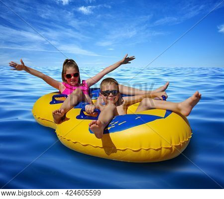 Boy and girl on inflatable float in blue sea water. Little children floating in yellow raft on surface wave.