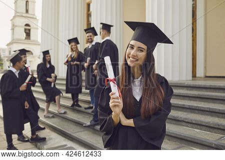 Happy Positive Pretty Girl University Graduate Standing Holding Diploma In Hand