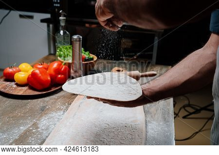 Mens Hands Hold A Thin Flatbread. Cooking Pizza, Noodles Or Pitta At Home