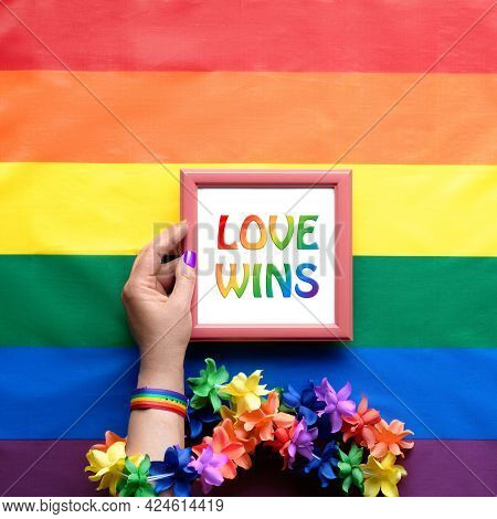 Text Love Wins In Hand, Flat Lay On Rainbow Flag With Flower Garland. Simple, Minimal Lgbt Pride Dec