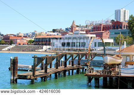 June 8, 2021 In San Francisco, Ca:  Rustic Wooden Pier With A Vintage Lifeboat And The Maritime Muse