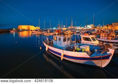 Venetian Fort Venetian fortress of Koules Castello a Mare castle in Heraklion and moored Greek fishing boats in port, Crete Island, Greece in the evening
