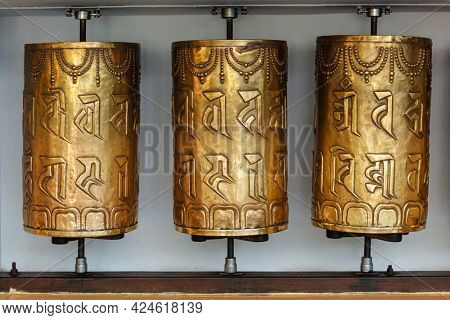 Metal buddhist prayer wheels with buddhist mantra Om mani padme hum meaning Praise to the Jewel in the Lotus in Tsuglagkhang complex in Dalai Lama residence. Mcleodganj, Himachal Pradesh, India
