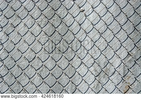 Fragment Of An Iron Mesh With Square Cells On A Gray Wall Background, For Use As An Abstract Backgro