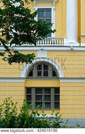 Arched Window And A Rectangular Window With A Balcony And White Columns Against A Yellow Wall. From
