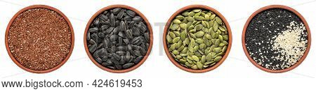 Set Of Pumpkin Seeds, Flax Seeds, Sesame Seeds And Sunflower Seeds In Bowls Isolated On White Backgr