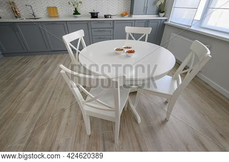 Beautiful dining area with white massive dining table and chairs for four