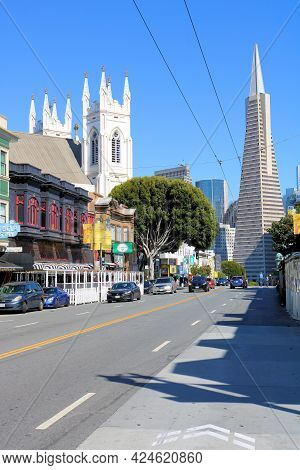 June 8, 2021 In San Francisco, Ca:  Retail Stores And A Cathedral With The Landmark Transamerica Bui