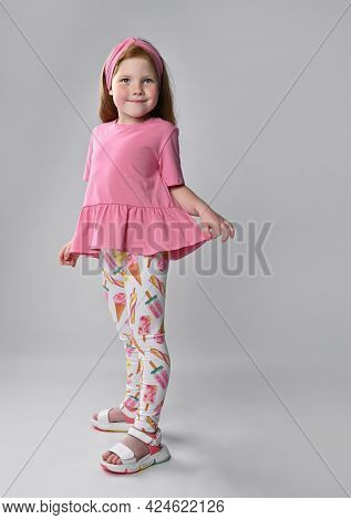 Little Red-haired Girl Touching Dress, Looking At Clothes Showing Summer Fashion Look. Advertising O