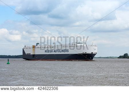 Stade, Germany - June15, 2021: Vehicles carrier HÖEGH Seoul on Elbe river heading to Hamburg. The vessel owned by Höegh Autoliners sails under Norwegian flag