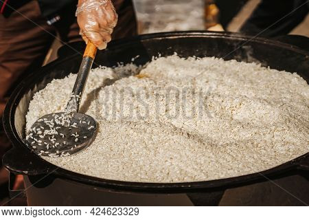 Cooking Of Freshly Pilaf In Large Metal Cauldron, Cook Mixes Rice With Scoop