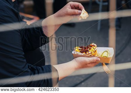 Hands Working Man With Sandwich Sprinkled With Ketchup And Mustard, View Through Metal Grate