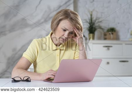 Portrait Of Tired Beautiful Elderly Senior Woman, Mature Adult Lady Freelancer Is Working On Laptop