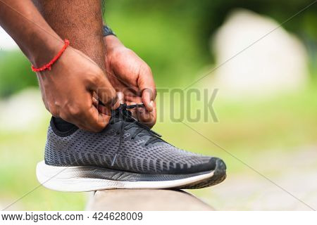 Close Up Asian Sport Runner Black Man Wear Watch Stand Step On The Footpath Trying Shoelace Running