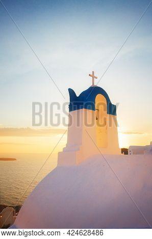 White  Church Belfry Over Sea At Sunset,  Oia, Santorini Island, Greece