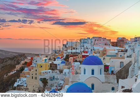 Cityscape Of Oia, Traditional Greek Village Of Santorini,  With Blue Domes Of Churches At Sunset, Gr