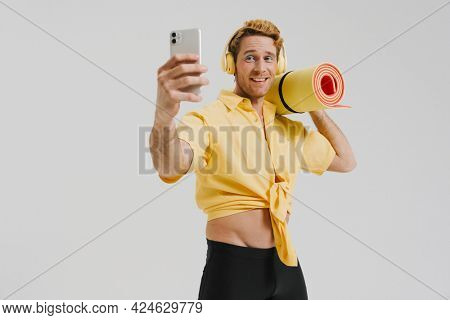 Smiling young white gay man carrying fitness mat listening to music with headphones standing over gray wall background taking a selfie