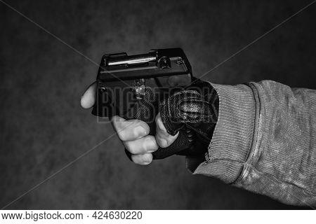 Self Defense Weapon In A Hand. Pepper Aerosol Pistol Over Dark Background.