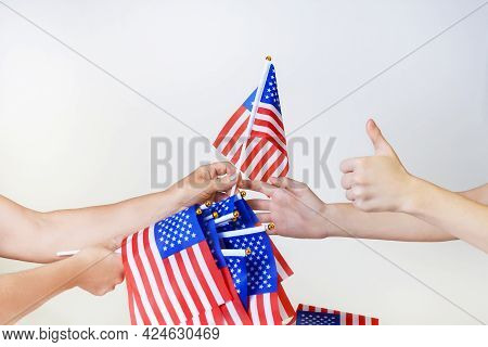 Hands Pass The American Flag Into The Hands Isolated On A Light Background. Stars And Stripes Flag S