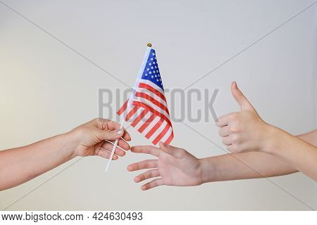 Hand Pass The American Flag Into The Hands Isolated On A Light Background. Stars And Stripes Flag Se
