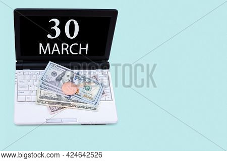 30th Day Of March. Laptop With The Date Of 30 March And Cryptocurrency Bitcoin, Dollars On A Blue Ba