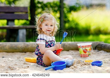 Cute Toddler Girl Playing In Sand On Outdoor Playground. Beautiful Baby In Red Trousers Having Fun O