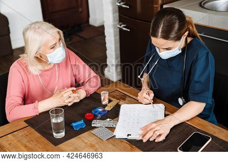 An overhead view of the positive female doctor in a protective disposable mask writing down the medical history on paper of her elderly patient at home