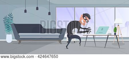 Thief In The Office. A Robber Steals Data From A Laptop. Security Concept. Thief Man Robbing An Offi