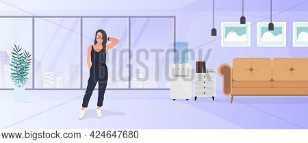 Model In A Stylish Suit. Brunette Girl Posing. Room, Sofa, Floor Lamp, Paintings On The Wall, Bookca