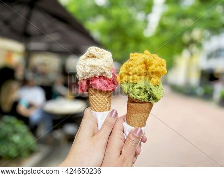 Young Woman Hands Holding Ice Cream Cones On Summer Day In The City. Tasty Colorful Fruit And Berry