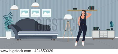 Brunette Girl Posing. Model In A Stylish Suit. Room, Sofa, Floor Lamp, Paintings On The Wall, Bookca
