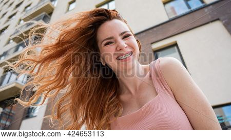 Beautiful Young Red-haired Woman With Braces On Her Teeth Smiling In The Summer Outdoors