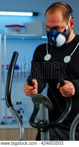 Athlete With Mask And Electrodes Attached On Body Running On Cross Trainer In Science Sport Lab Moni