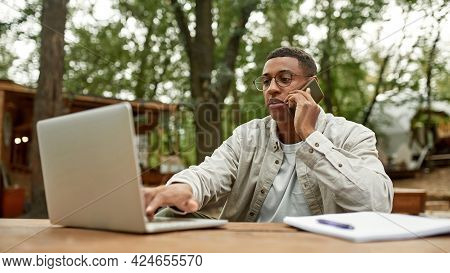 Young African American Man Talking On Phone In Front Of Laptop While Sitting At Wooden Table Outdoor