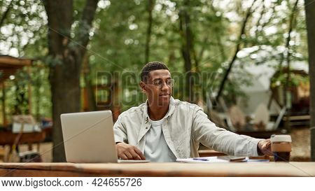 Smiling Young African American Man Working On Laptop While Sitting With Coffee At Wooden Table Outdo