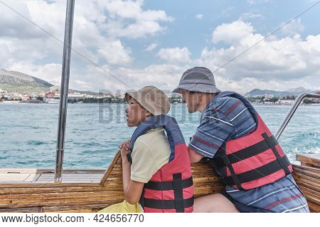 An Asian Boy And Older Man, His Grandfather, In Life Jackets Trip On Pleasure Boat On The Sea.