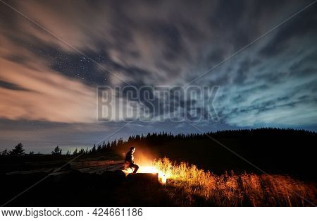 Man Hiker Looking At Bright Campfire While Sitting On Wooden Planks Under Magnificent Night Sky With