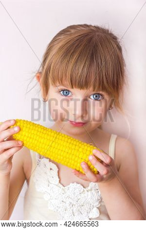 Close-up Portrait Of A Little Beautiful Girl With Blue Eyes And Boiled Corn In Her Hands