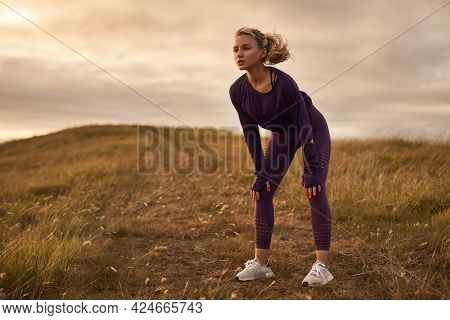 Full Body Of Young Female Jogger In Stylish Sportswear And Sneakers Having Break And Leaning On Knee