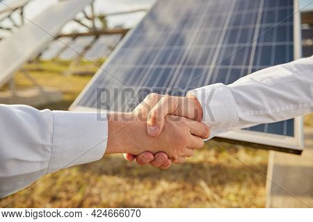 Crop Anonymous Male Business Partners Shaking Hands As Symbol Of Agreement While Standing Near Photo