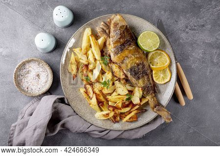 Baked Sea Bass Or Lingcod Fish With Potatoes On A Plate And Gray Background Top View