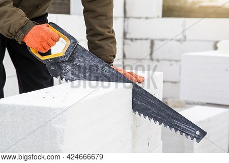 Closeup. Builder Sawing Aerated Concrete Block With Hand Saw At Construction Site. Construction, Bui