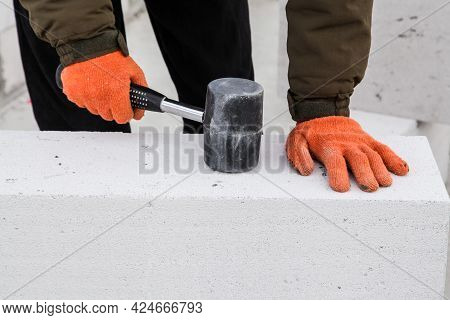 Construction Worker Beating Aerated Concrete Block With Rubber Hammer. Building Manual Work
