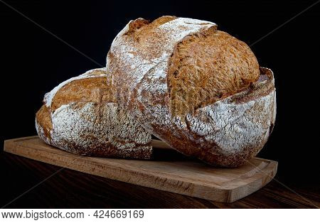 Two Loaves Of Rustic Bread On A Wooden Board. Homebaked Bread .