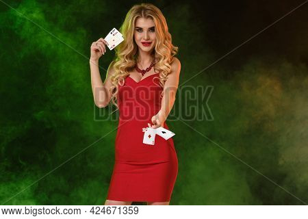 Blonde Lady In Red Dress. Smiling, Holding Or Throwing Something, Showing Two Aces, Posing On Colorf