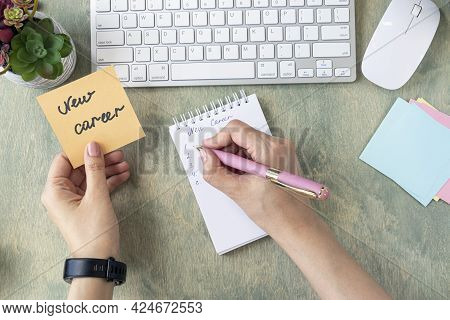 Business And Finance Concept. Female Hands Hold Note With Words New Career And Writing In Notepad On