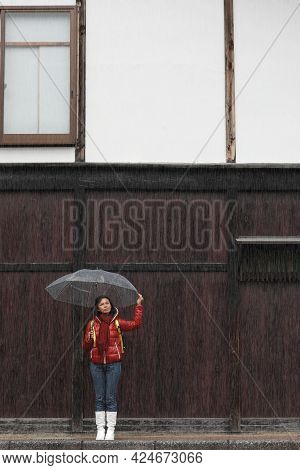 Woman With Transparent Umbrella In Rainy With Wood Wall Background. Rainy Season Concept.