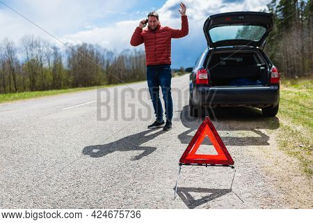 Angry Man Calling Repair Service After Car Breakdown.youg Man Talking On Cell Mobile Phone On Road.